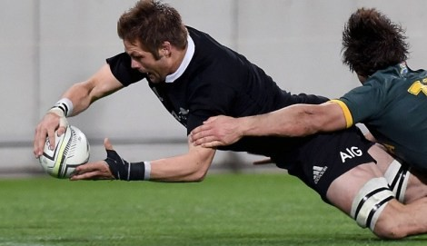 New Zealand's openside flanker captain Richie McCaw (L) scores a try as he is tackled by South Africa's outside centre Jan Serfontein during the Rugby Championship Test between New Zealand and South Africa at Westpac Stadium in Wellington on September 13, 2014.   AFP PHOTO / MARTY MELVILLE